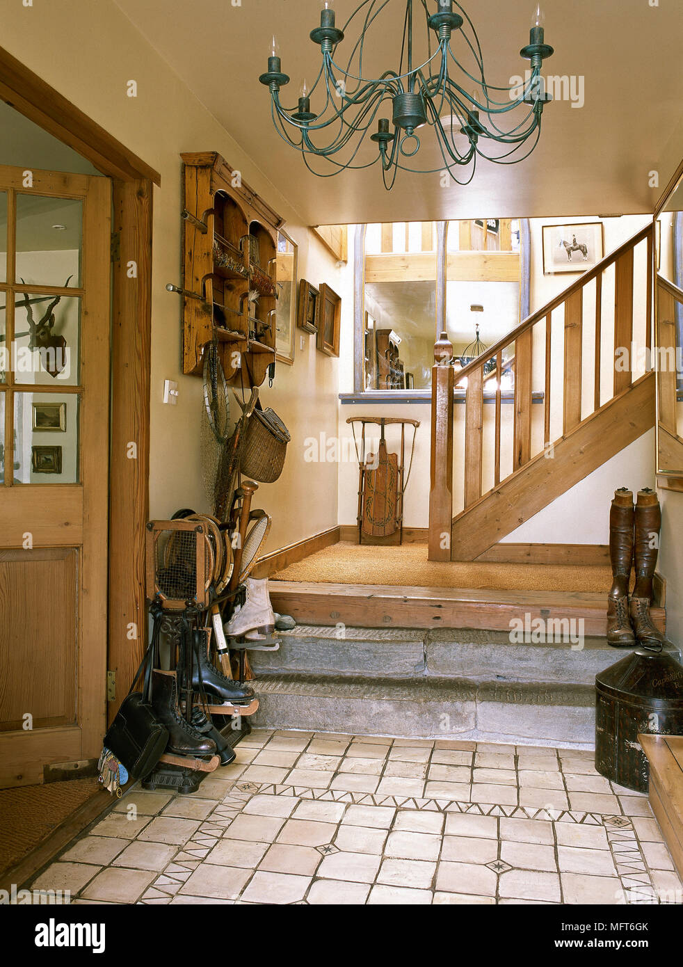 Country Entryway With Mosaic Tile Floor, Wooden Stairway, Chandelier, And A  Variety Of Boots And Shoes.