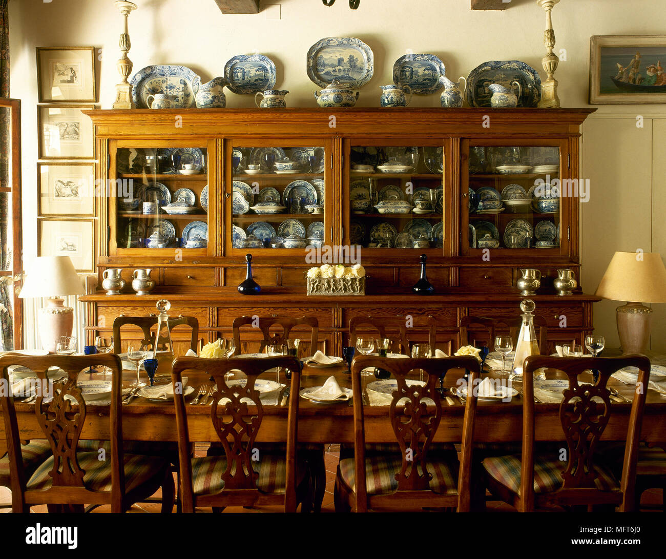Traditional Dining Room Suite With Table, Chairs, And An Antique Cabinet  Displaying A Collection Of China.