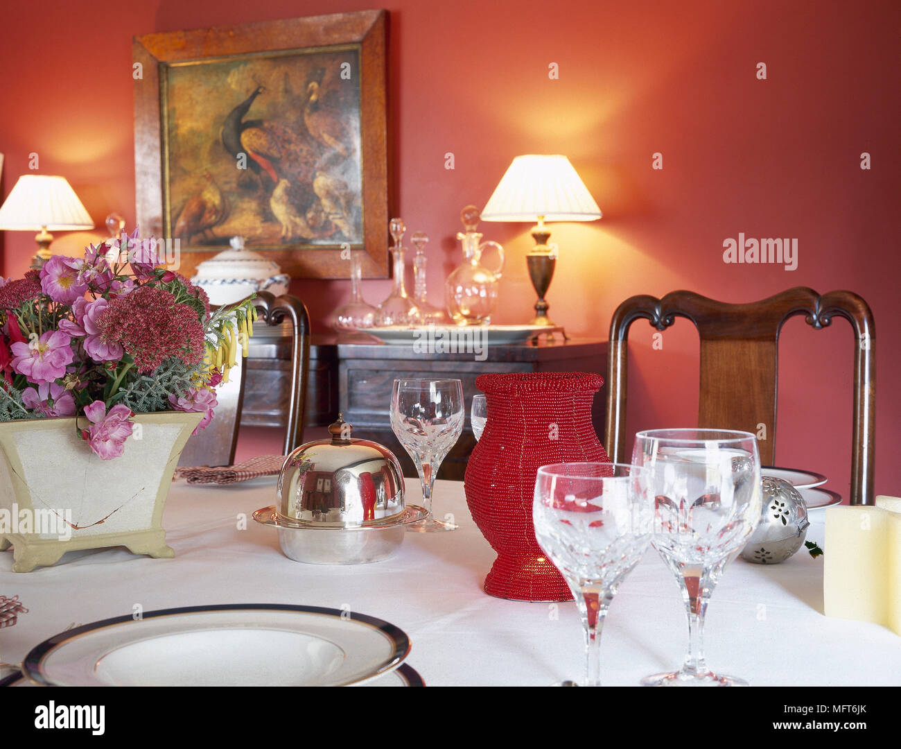 Picture of: Traditional Red Dining Room Detail Of A Dining Table With Table Settings And Lit Table Lamps On A Buffet Stock Photo Alamy