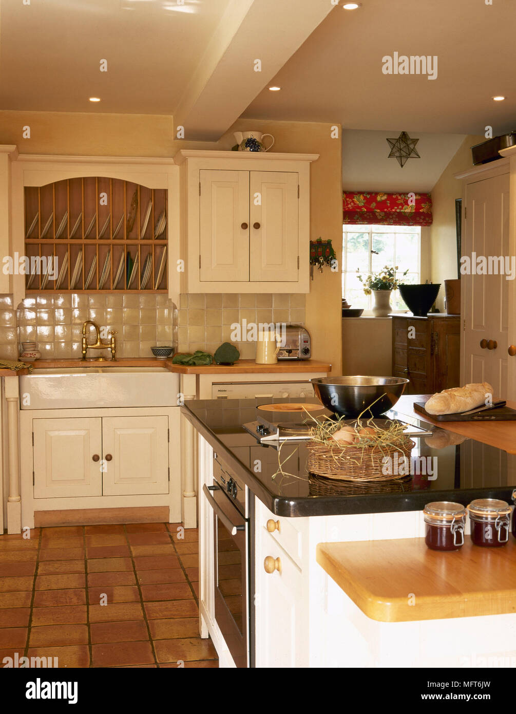 Country kitchen with tile floor, painted cabinets, apron sink, central island, and recessed lighting. - Stock Image