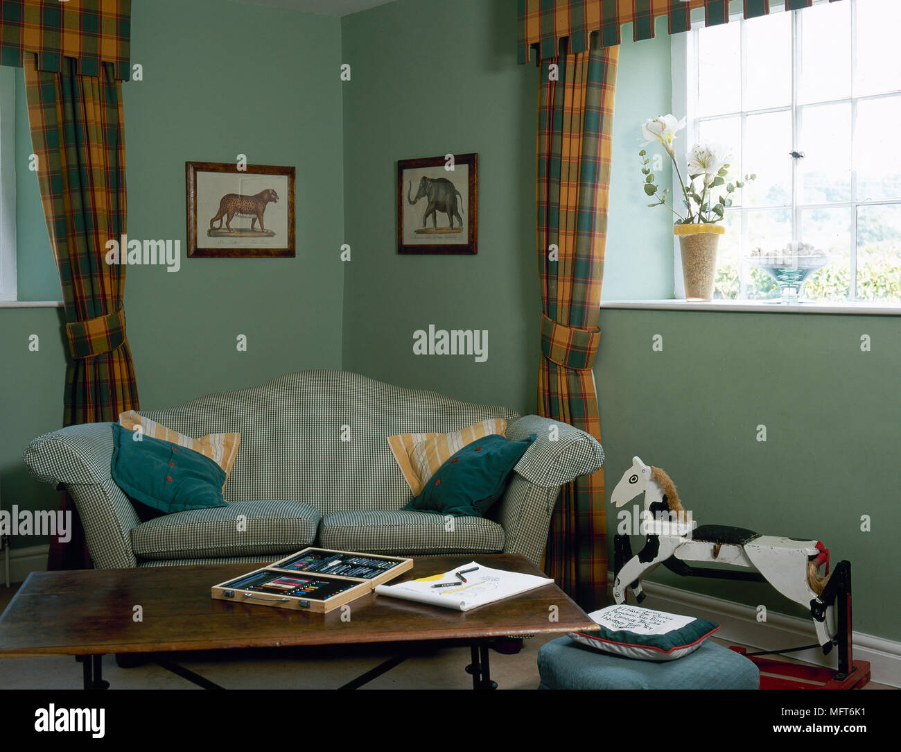 Country sitting room with green painted walls plaid window treatments sofa coffee table and antique rocking horse interiors rooms window treat