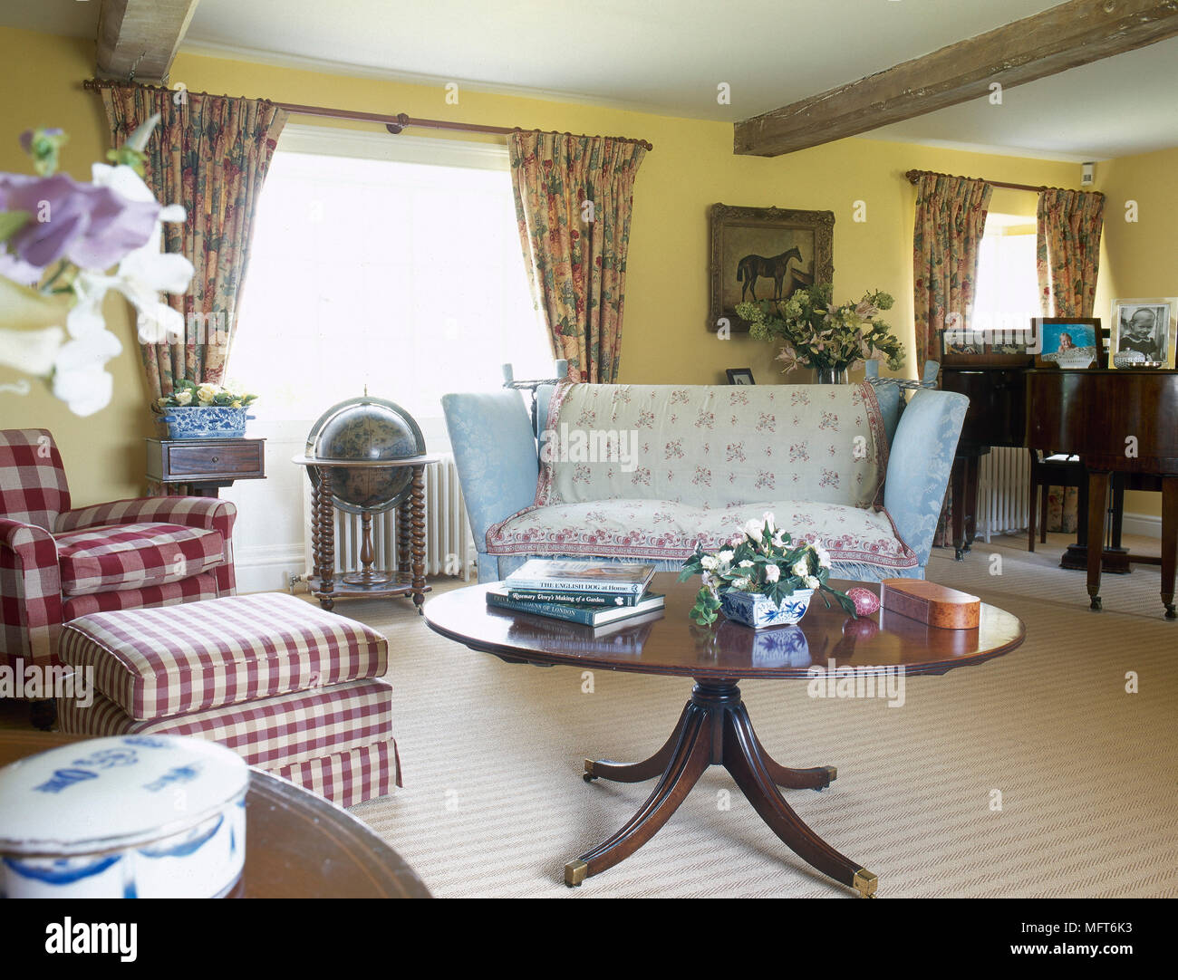 Country Cottage Sitting Room With A Beamed Ceiling, Floral Curtains,  Pedestal Coffee Table, And An Upholstered Sofa And Chair.