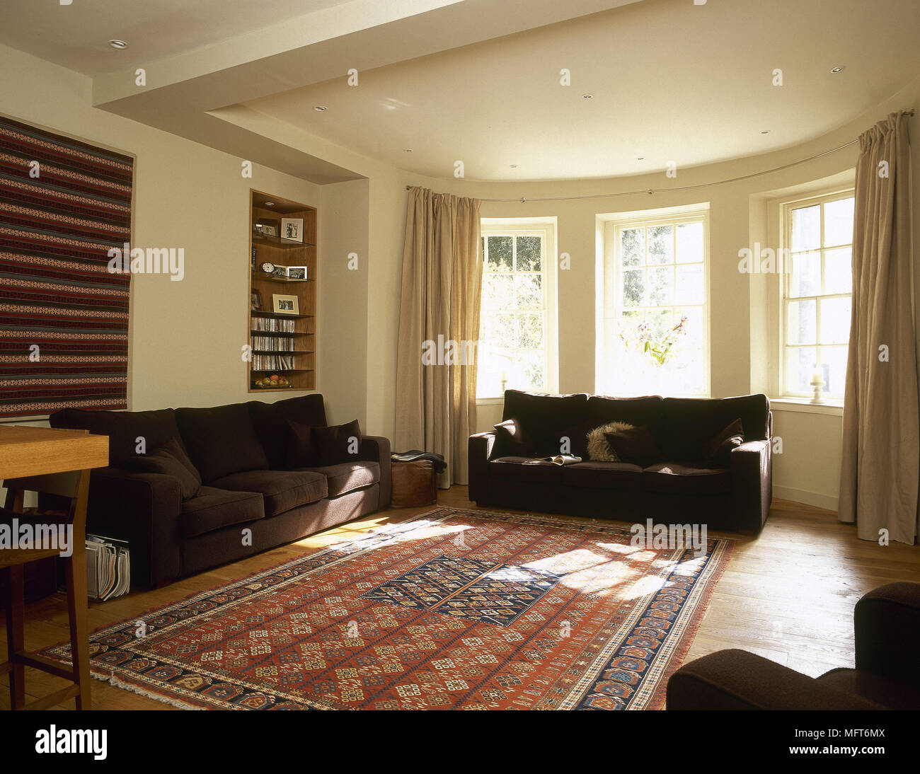 Upholstered sofa in front of bay window Stock Photo