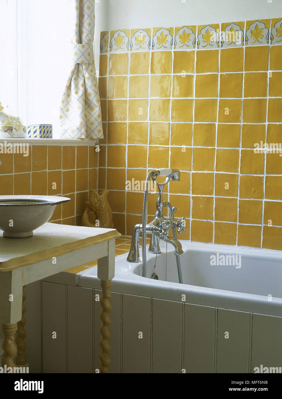 Bathroom with wooden panelling and yellow tiles around bath Stock ...