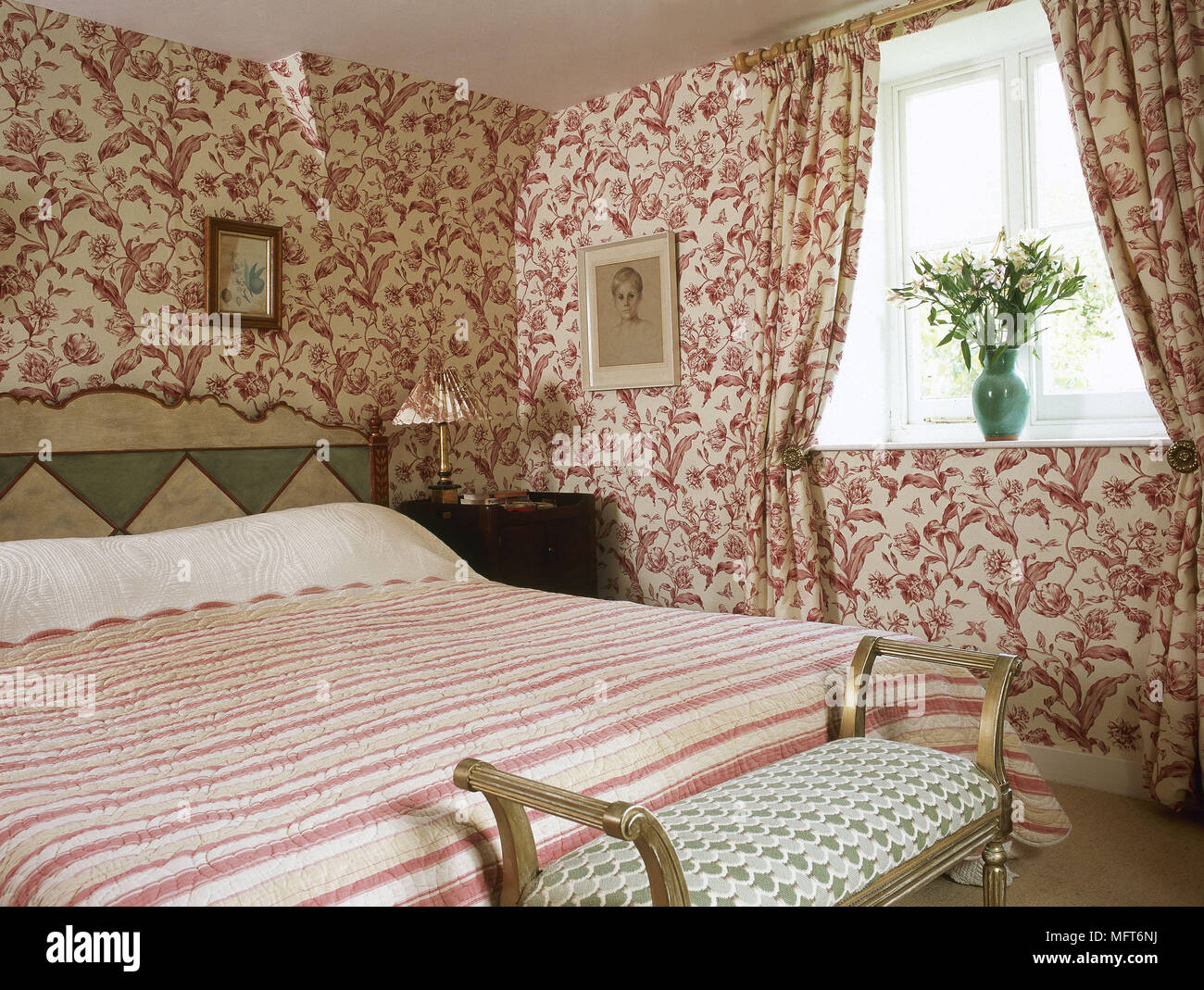 Bedroom with patterned wallpaper and coordinating curtains - Stock Image