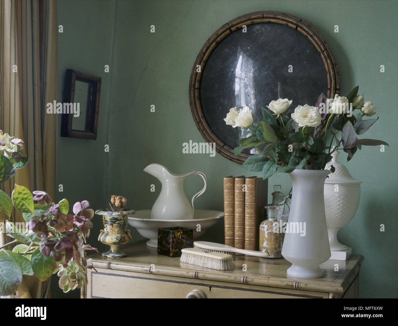 A detail of a traditional green bedroom a bamboo cane chest of drawers with wash basin and ewer Stock Photo