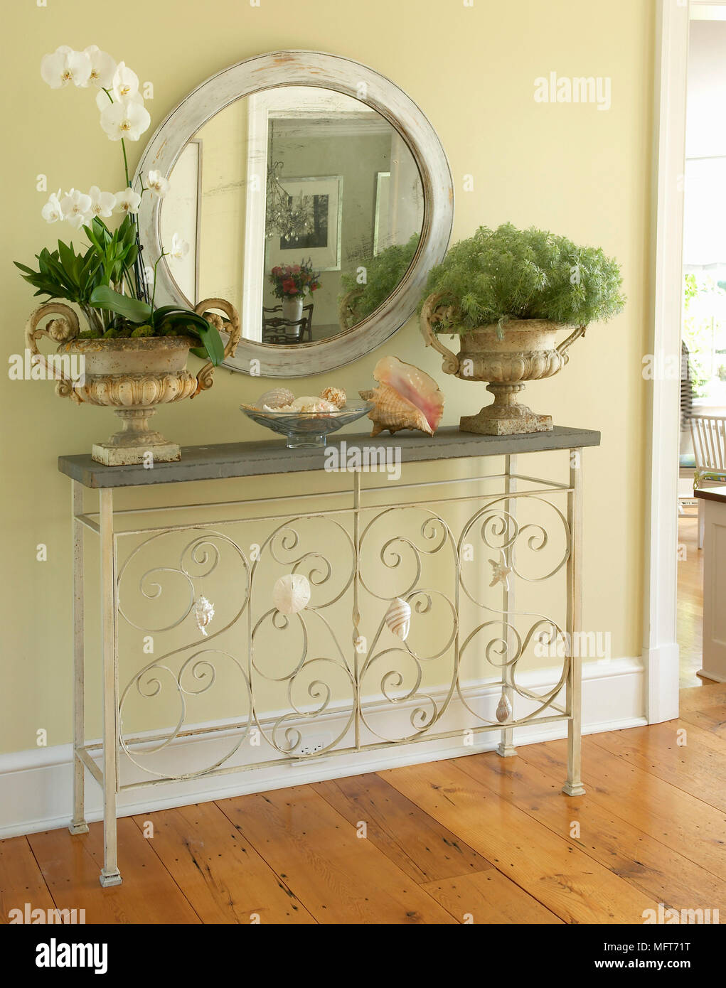 Pair Of Stone Urns Either Side Of Mirror On Metal Hall Table