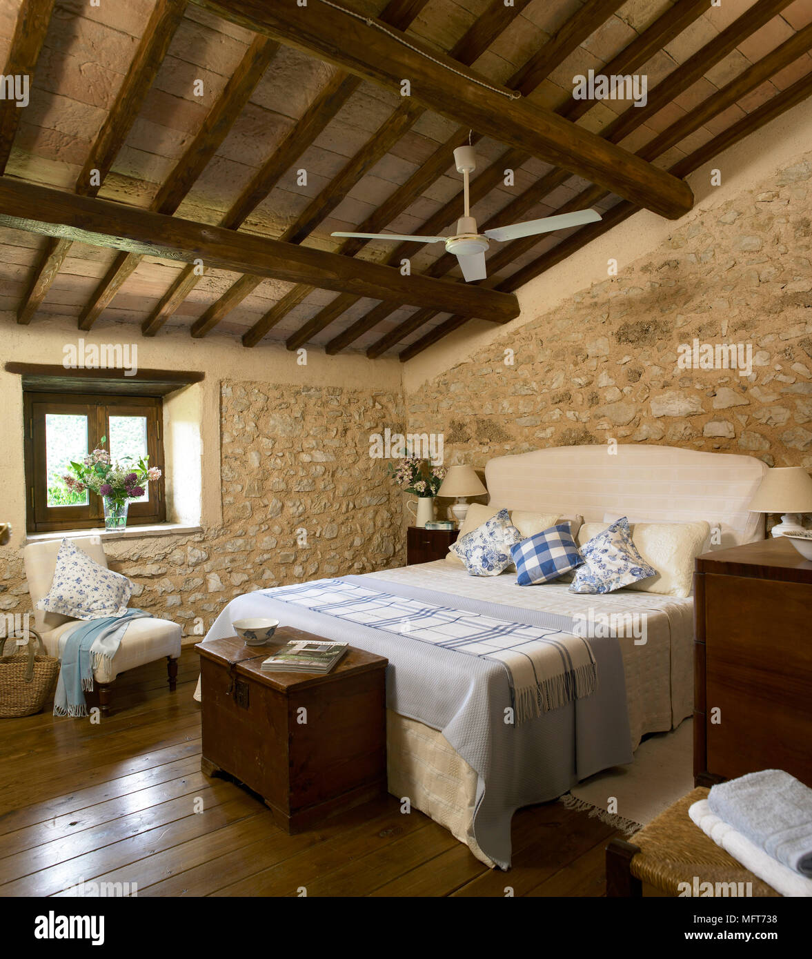 A country bedroom with exposed rustic stone walls and beamed ceiling double bed with - Camera stile country ...
