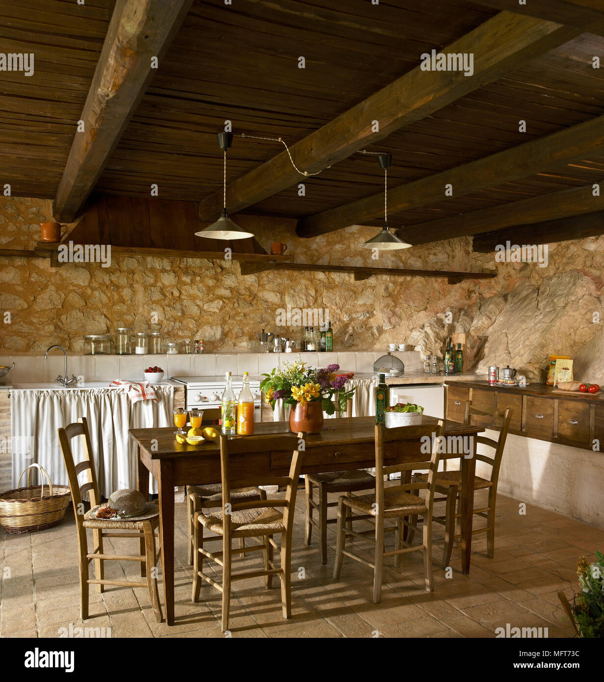 a country kitchen with exposed rustic stone walls and beamed ceiling