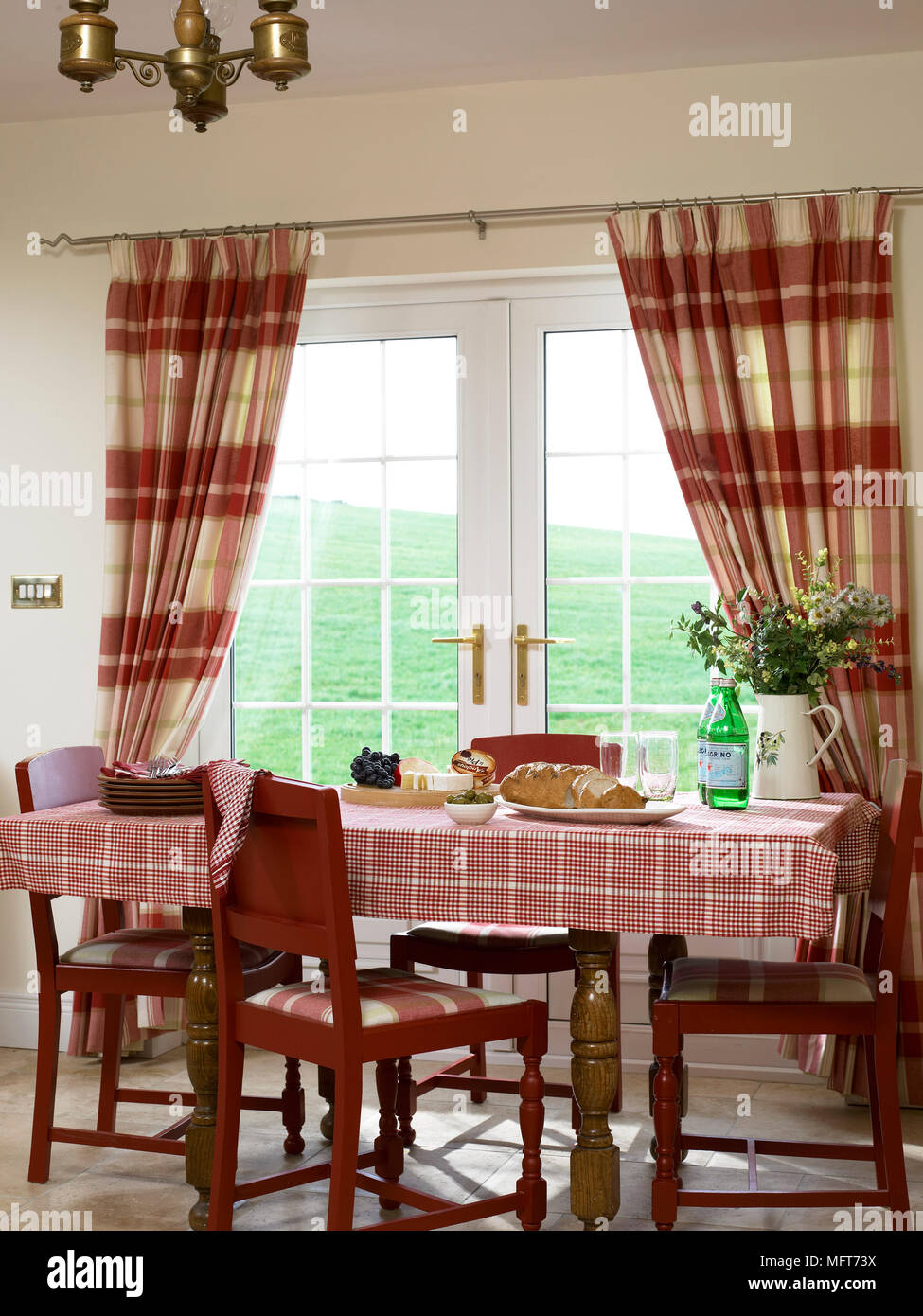 A Traditional Country Dining Room Wooden Table And Chairs Check Curtains At French Windows Stock Photo Alamy
