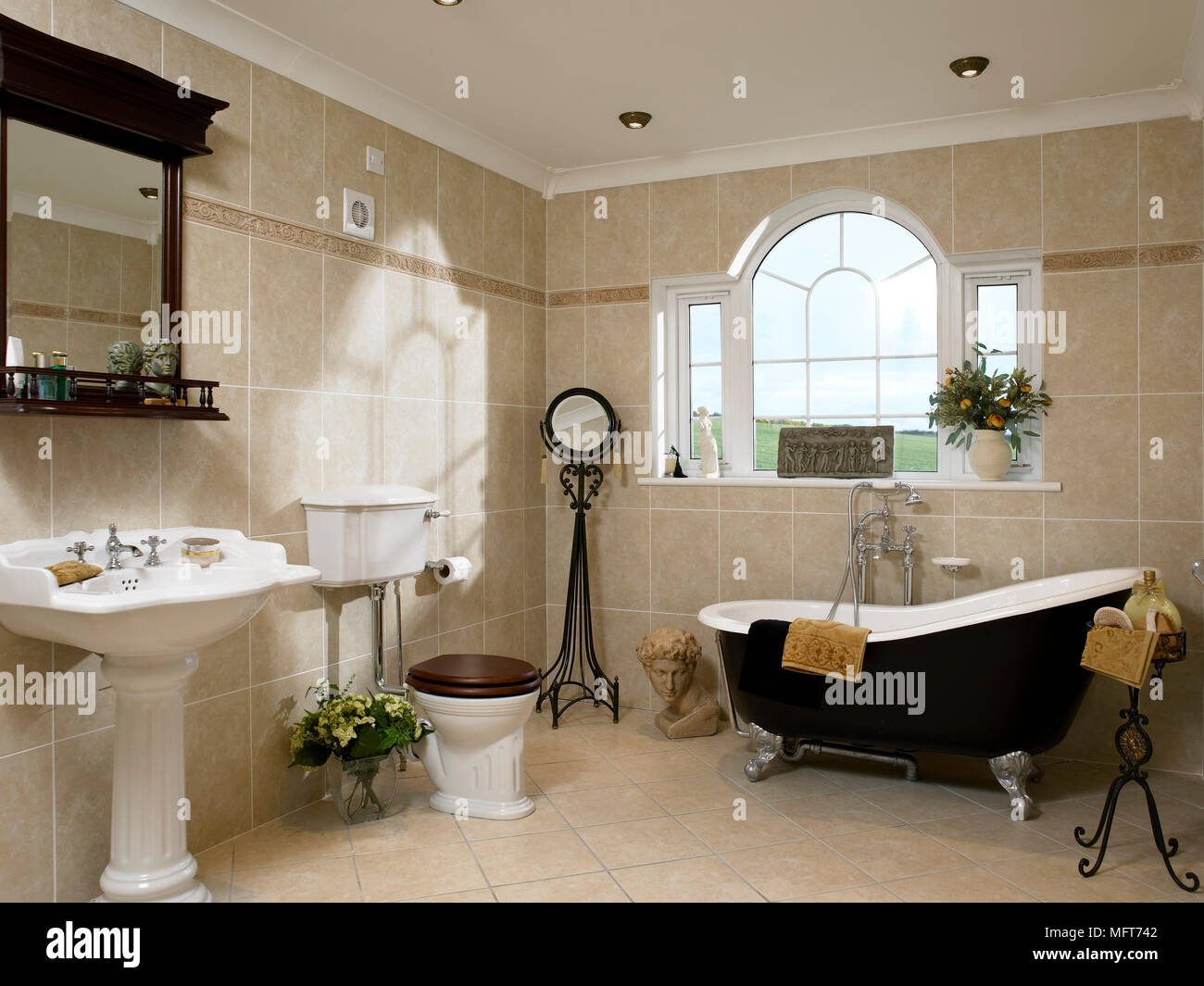 A traditional style bathroom with tiled walls, a freestanding roll ...