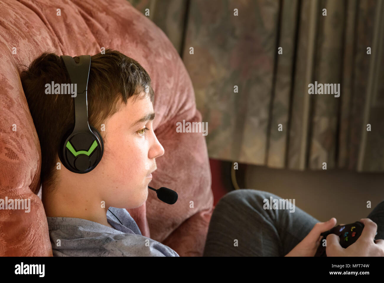 Teenage boy sits engrossed on a comfortable armchair with an x box controller in his hands and headphones plus microphone on his head. - Stock Image