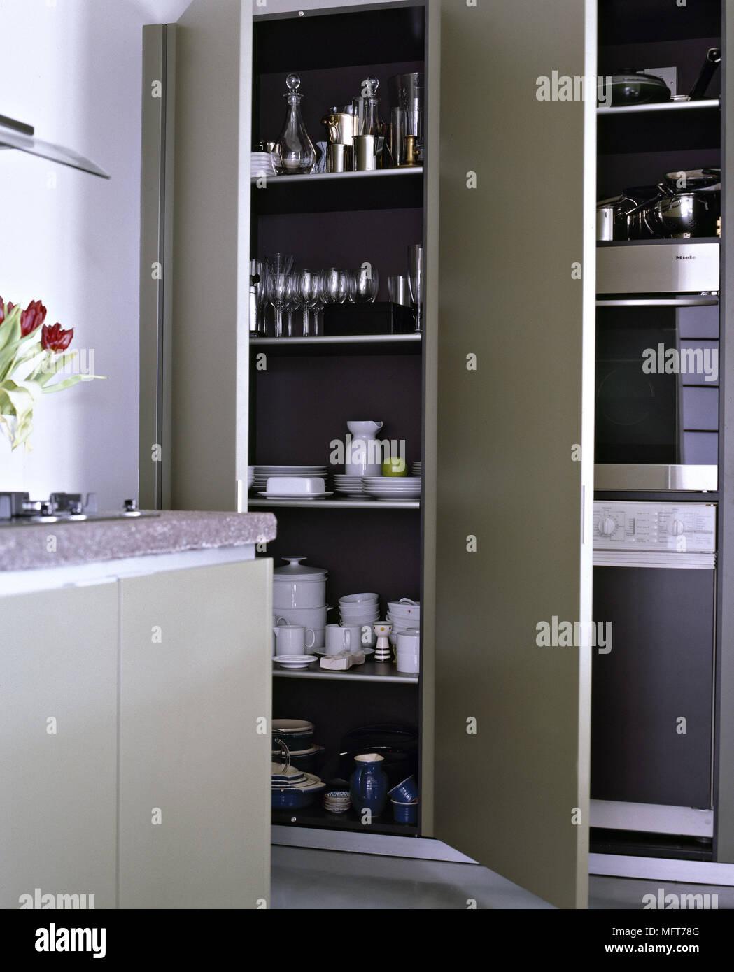 A detail of a modern green kitchen storage units doors open ...
