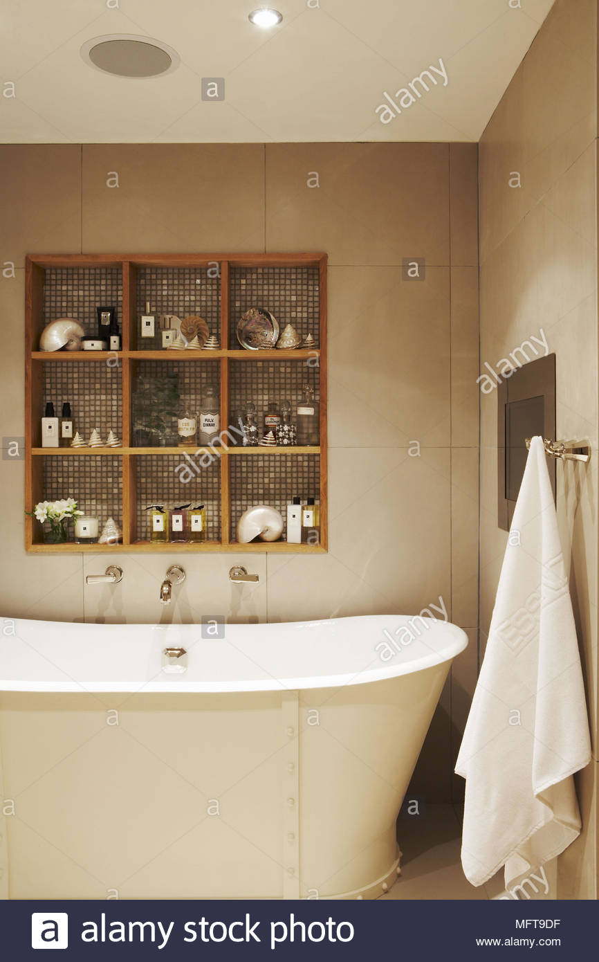 Toiletries set in recessed shelving above contemporary roll top bath ...