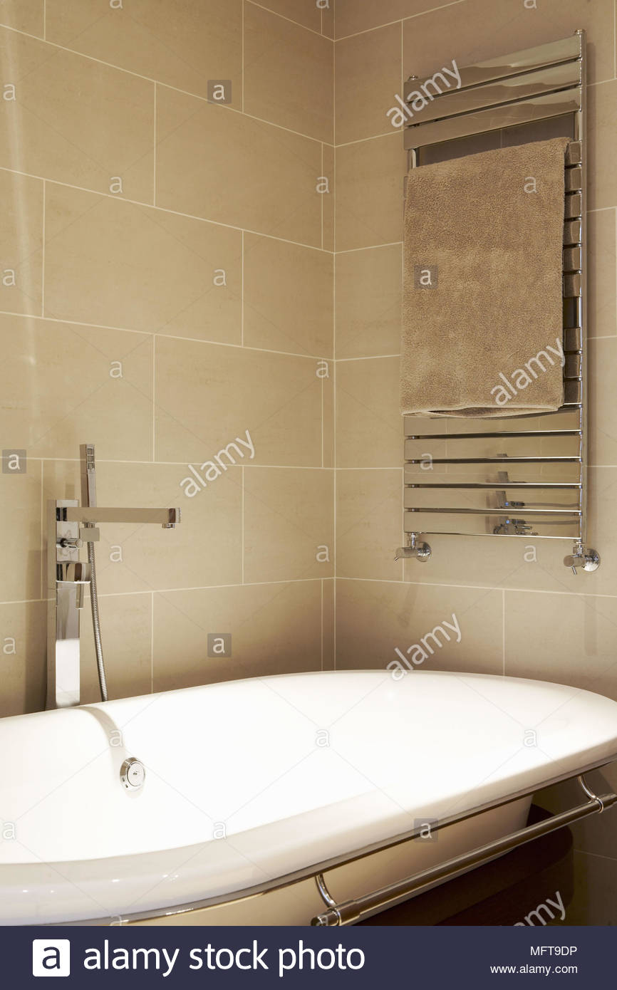 Towel rail radiator above freestanding contemporary bathtub Stock ...