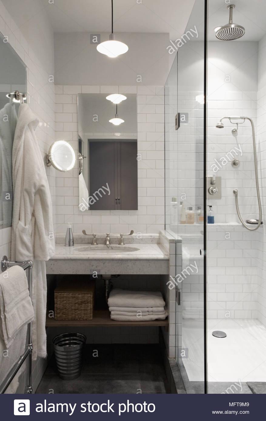 Washbasin set in granite shelf next to shower unit with glass screen ...
