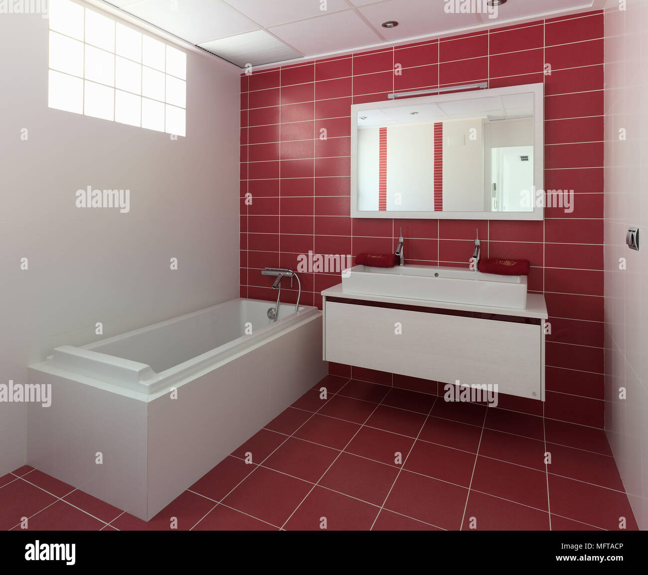 Washbasin on wall mounted unit next to bathtub in modern red bathroom Stock Photo