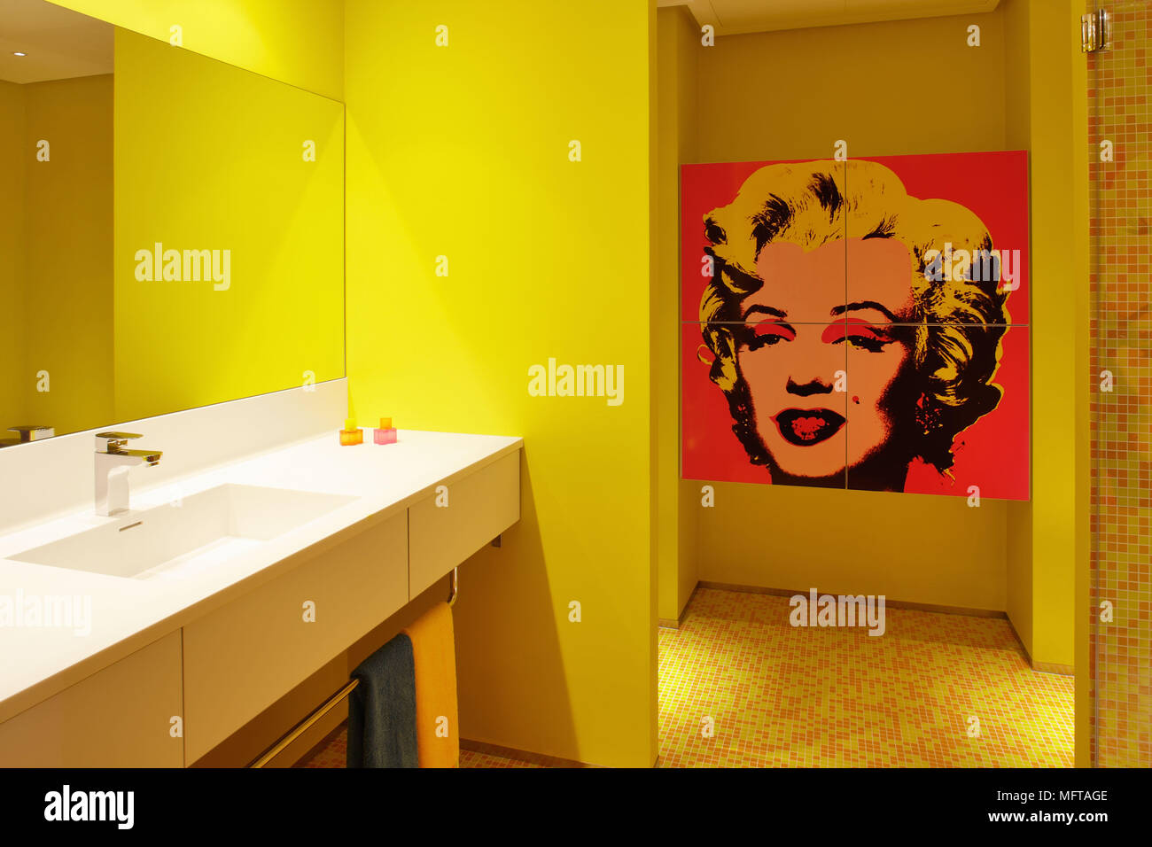 . Mirror above washbasin set in shelf unit in contemporary yellow