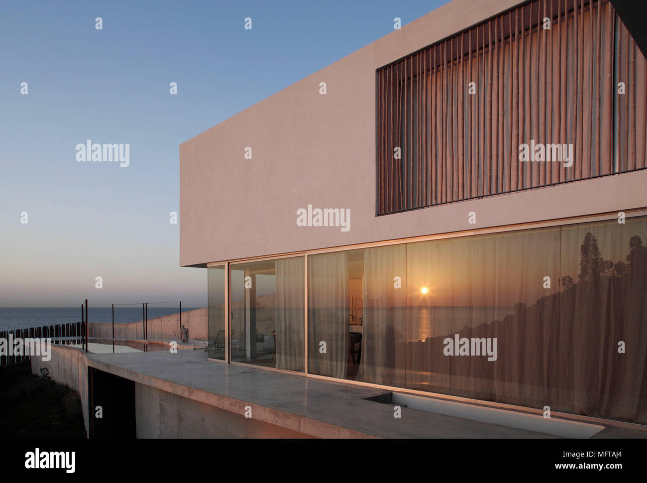 Exterior of modern house overlooking ocean with setting sun reflected in window Stock Photo