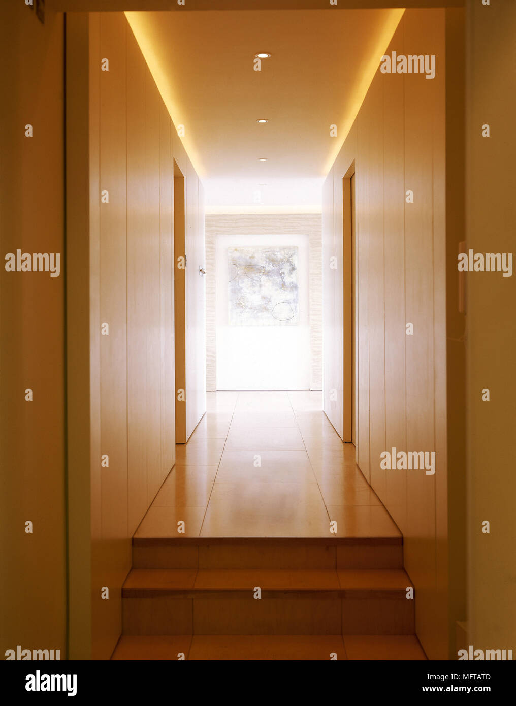 Steps up to a modern hallway with a tiled floor, doorways, wooden panelling, and ambient lighting. - Stock Image