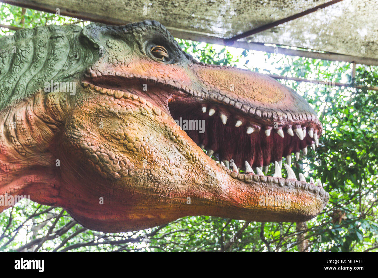 photograph of a wooded area where a green mechatronic dinosaur is below a sail cloth roof - Stock Image