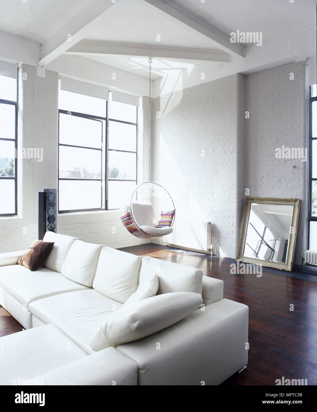 Loft Sitting Room With Sectional Sofa, Hanging Seat, Wood Floor And Sunny  Windows.