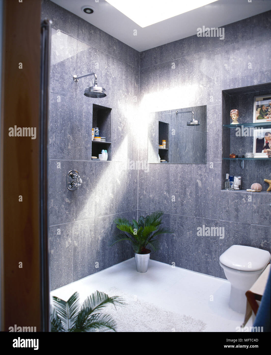 Modern, grey tiled bathroom with open shower, niche shelving, and ...