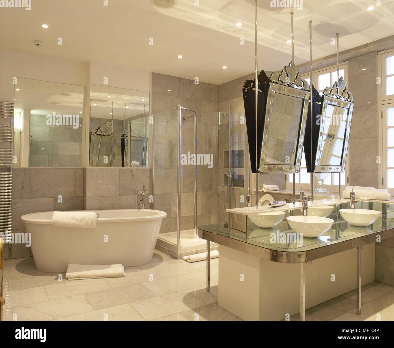 Spacious, tiled bathroom with twin washbasins on a centre island, a ...