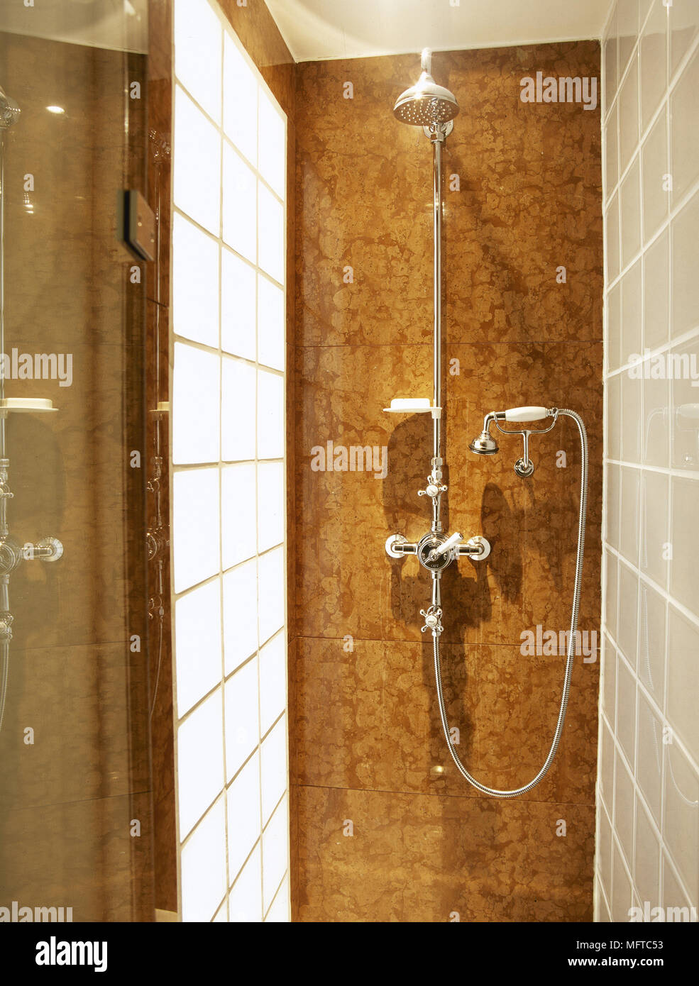 . Modern bathroom detail of a shower stall with tile walls and a glass