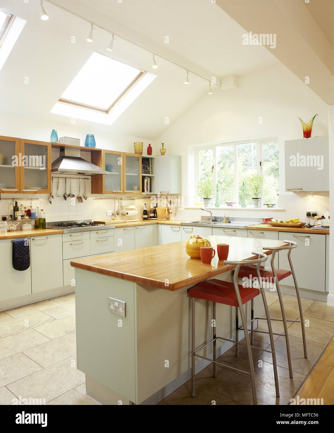 Modern Kitchen With White Cabinets Central Island Breakfast Bar Tile Floor And A Pitched Ceiling With Skylights Stock Photo Alamy