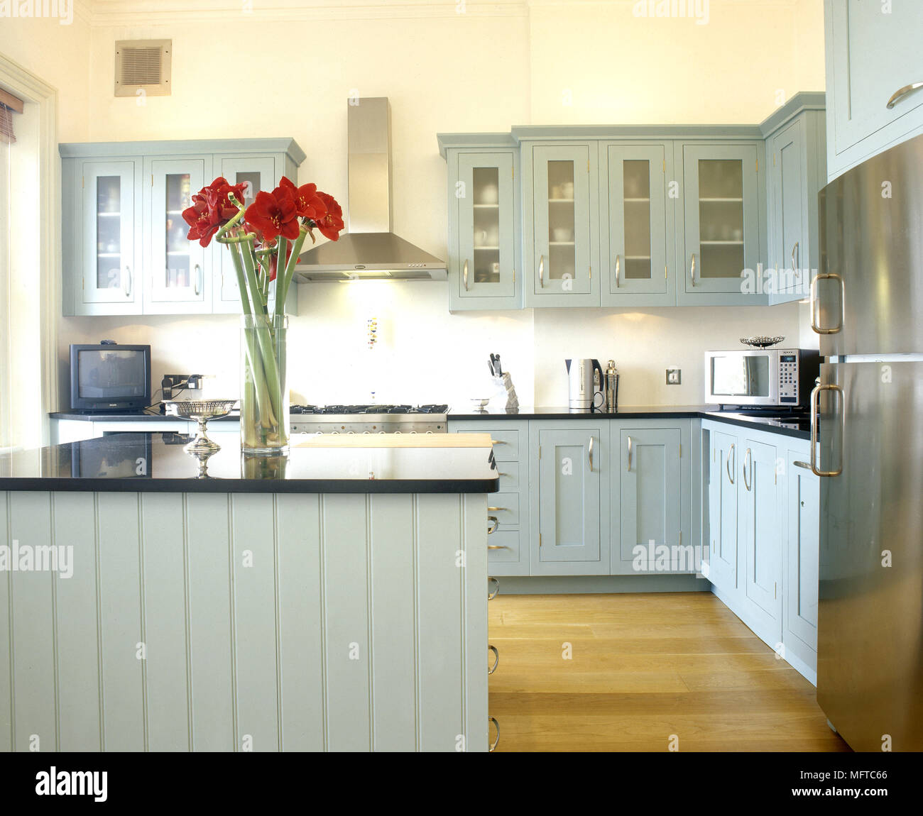 Modern Country Kitchen With Green Painted Glass Front Cabinets Central Island And Wood Floor Stock Photo Alamy
