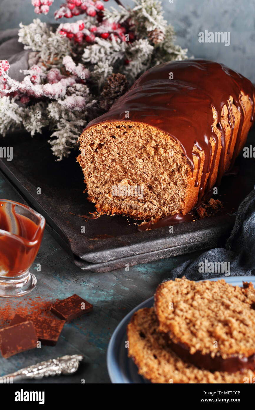 cut of homemade chocolate bread with chocolate icing, in New Year's decorations - Stock Image