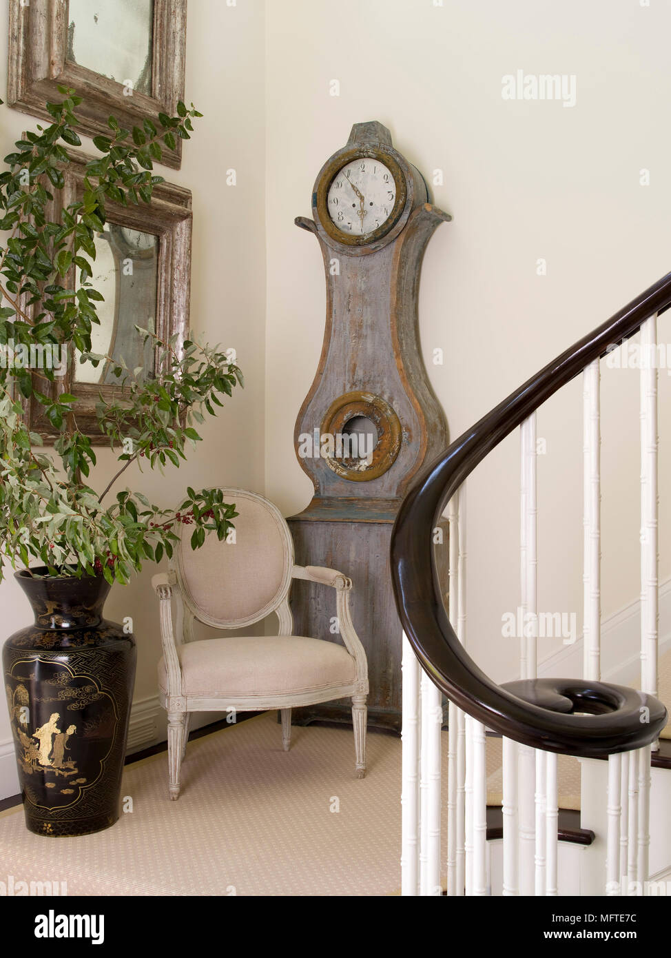 Period Style Chair In Front Of Gustavian Style Clock In Hallway