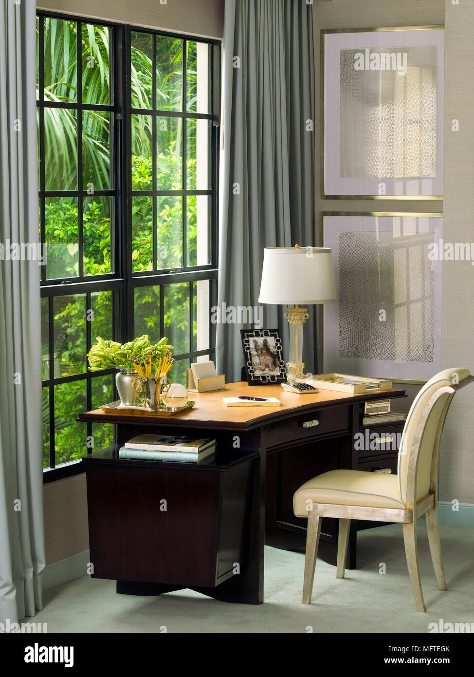 upholstered chair at desk in front of window in corner of room stock rh alamy com desk in front of window feng shui desk in front of window with curtains