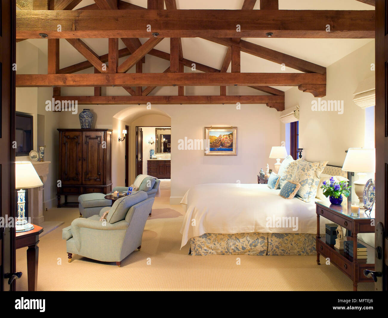Pair of armchairs at foot of double bed in traditional style bedroom Stock Photo