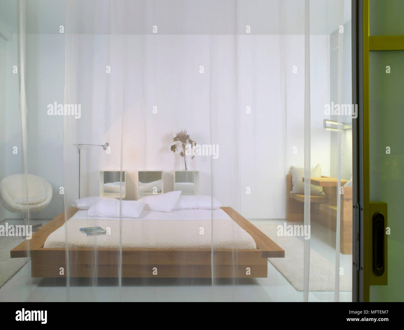 Wooden Platform Bed In Modern Bedroom Seen Through Sheer Curtain Stock Photo Alamy