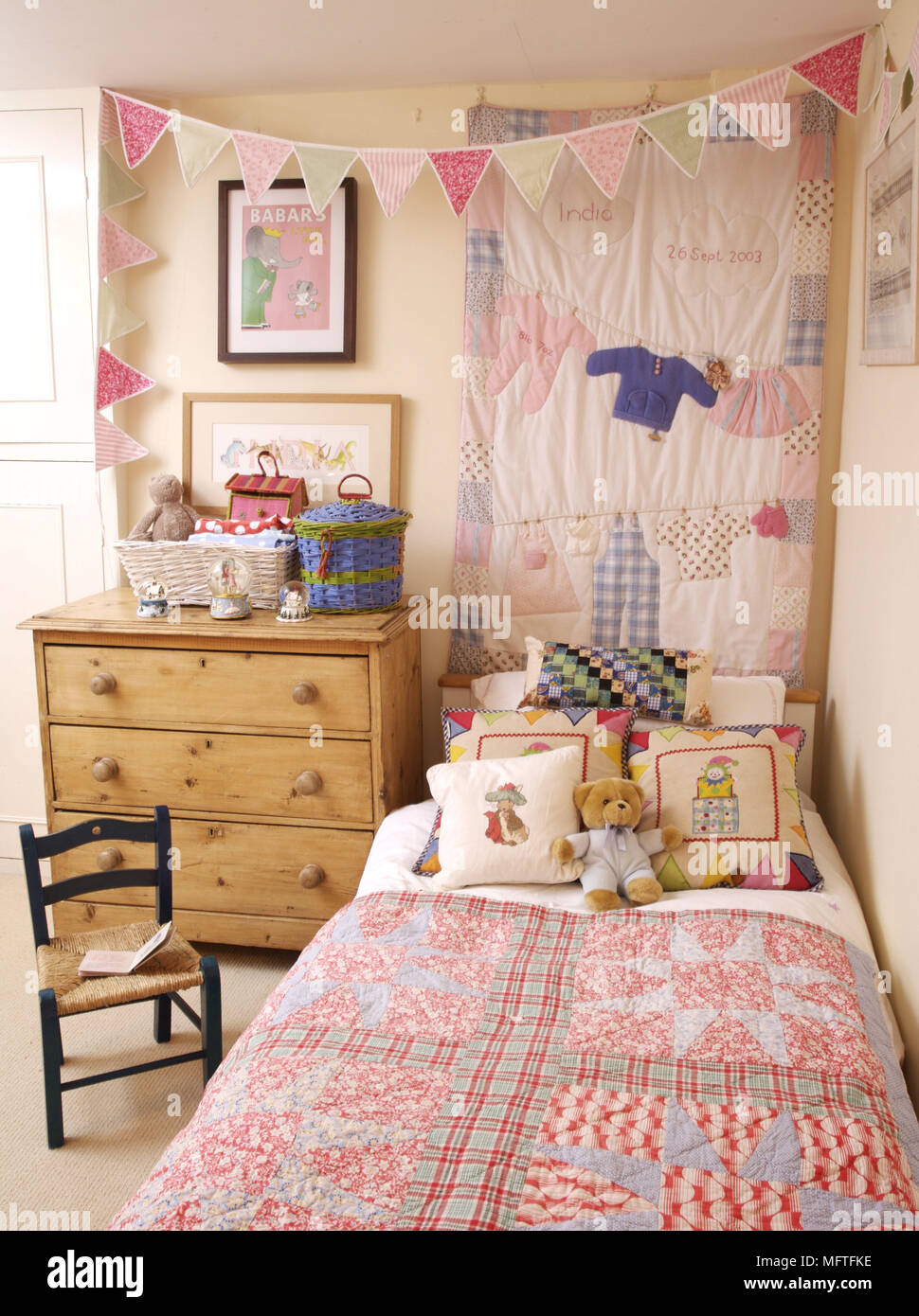 Pine chest of drawers next to single bed in childs bedroom - Stock Image