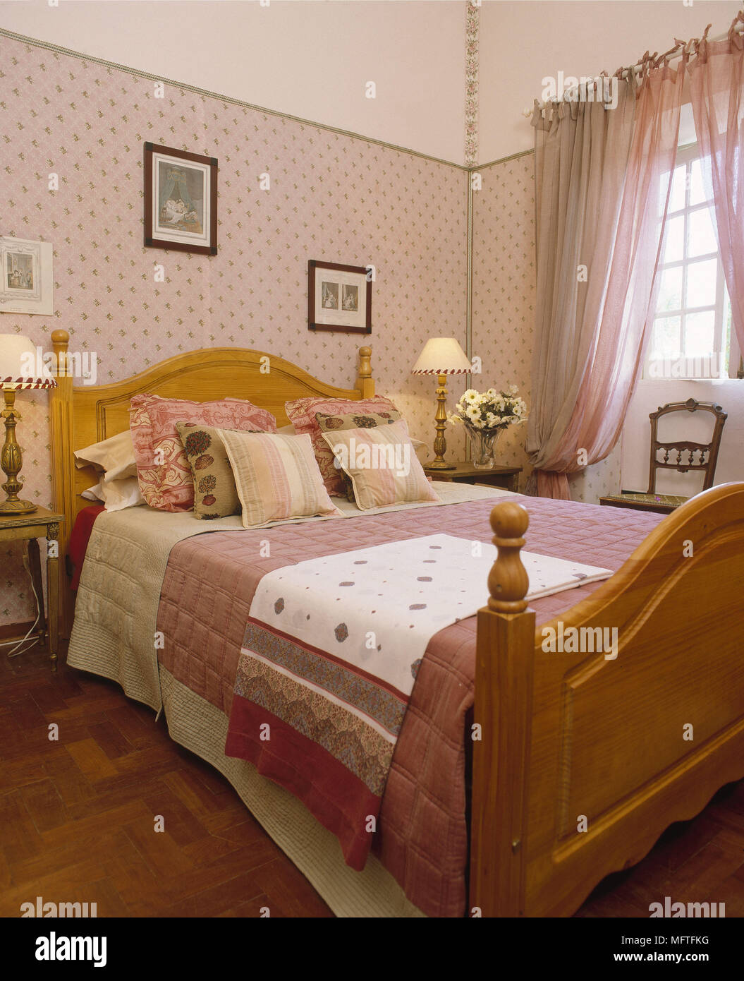 Pine double bed in pink bedroom - Stock Image