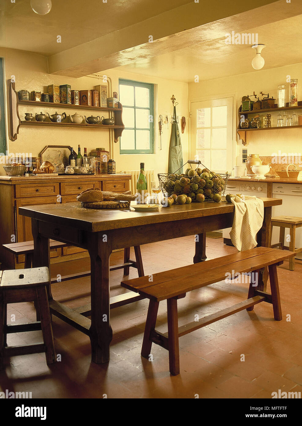 Traditional Dining Room Yellow Walls Wood Units Filled Shelves Table Bench Stools Interiors Kitchens Country Pendant Ceiling Lights Wine Bottles Kitc