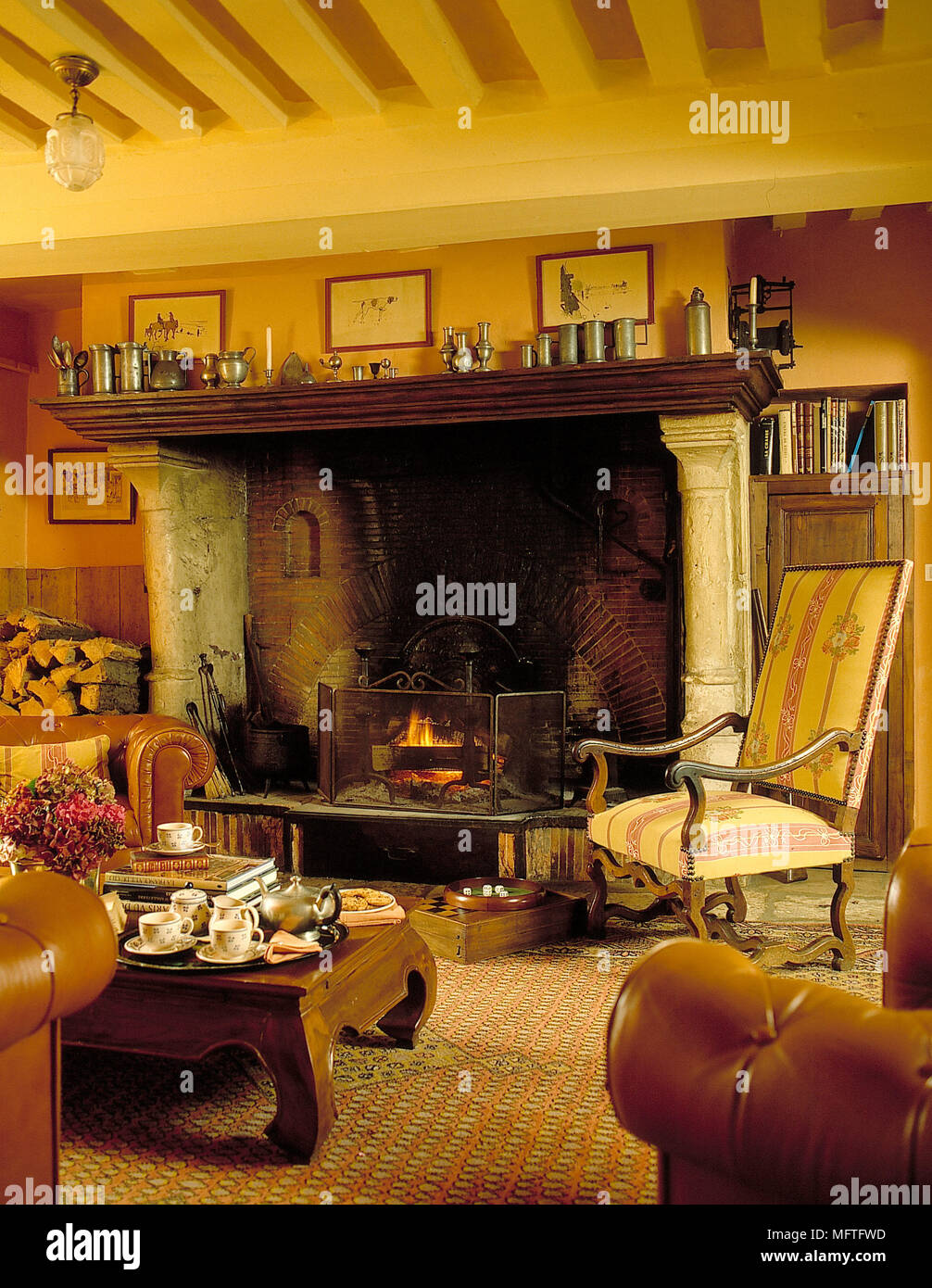 Traditional sitting room yellow walls beamed ceiling lit fire in
