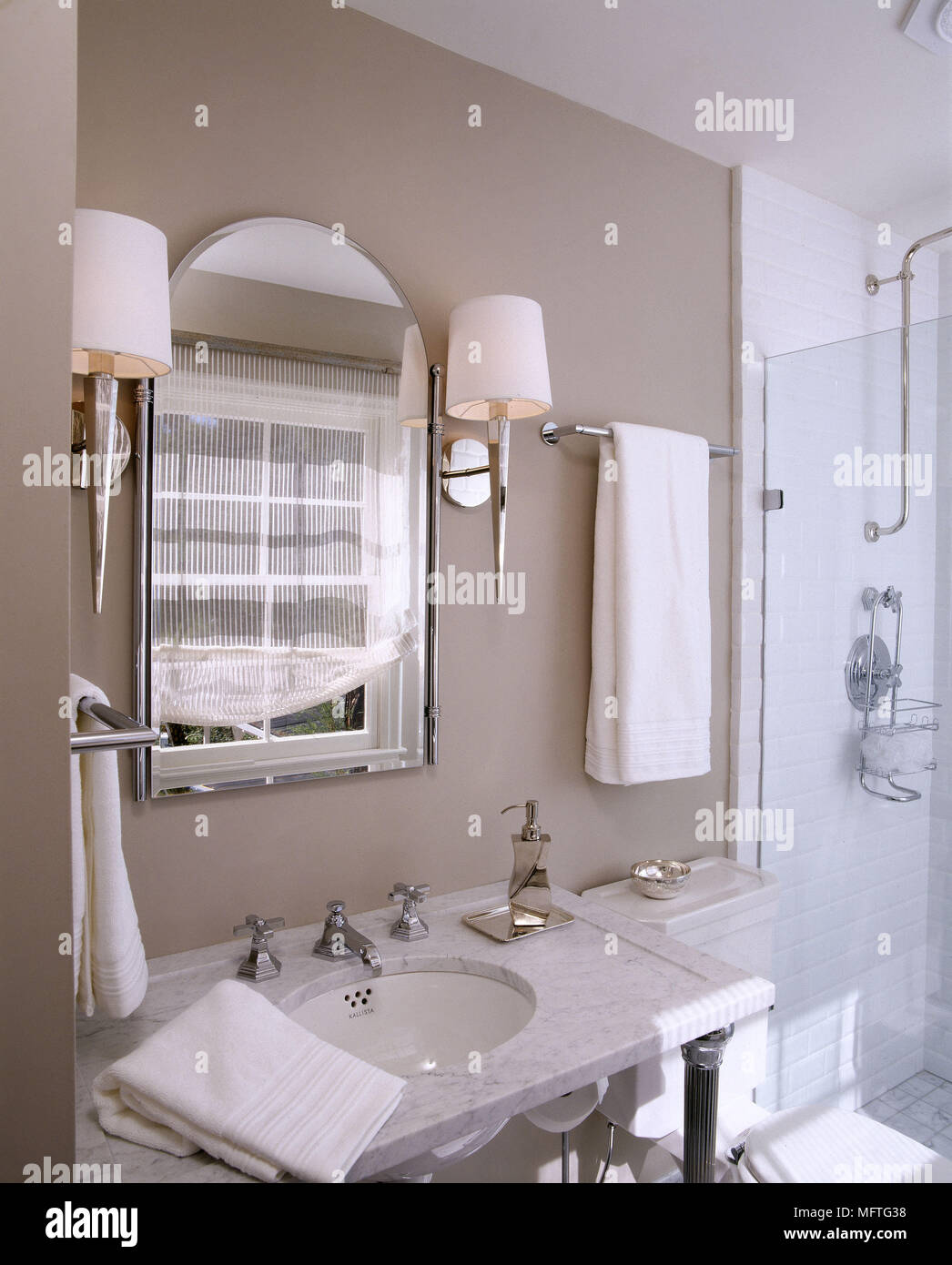 Bathroom with washbasin set in marble surround and shower cubicle ...