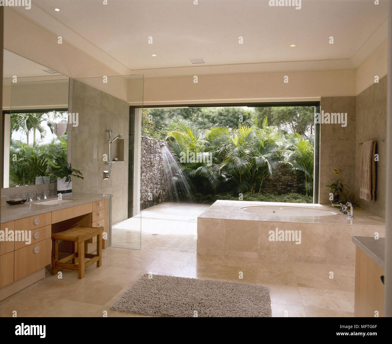 Modern bathroom with tiled bath and open shower area USA Stock Photo ...