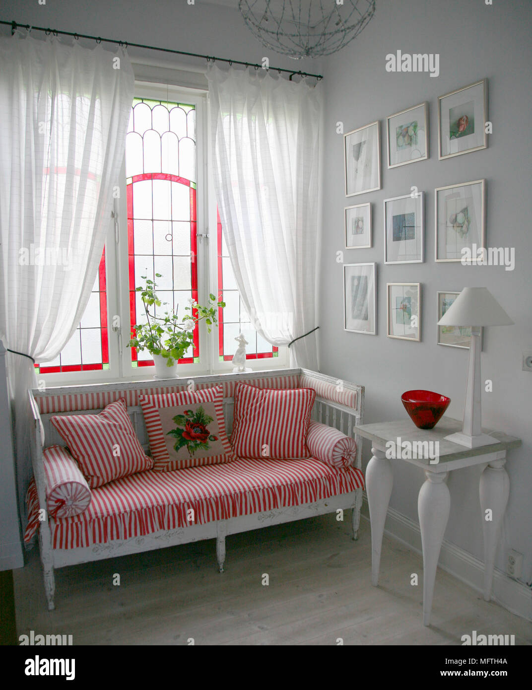 Swedish Style Sofa With Red Stripe Cushions Beneath Window With Sheer  Curtains