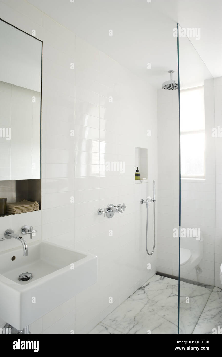 Wall mounted washbasin next to shower cubicle in modern bathroom ...