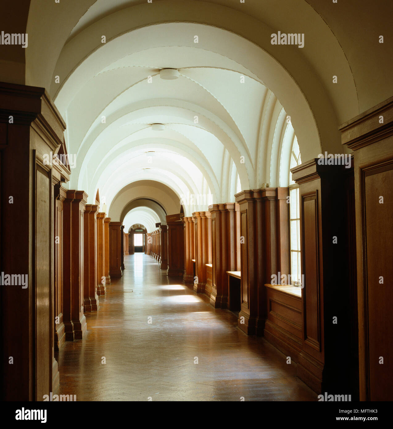 Long Corridor With Wooden Panelled Walls And Arched Ceiling