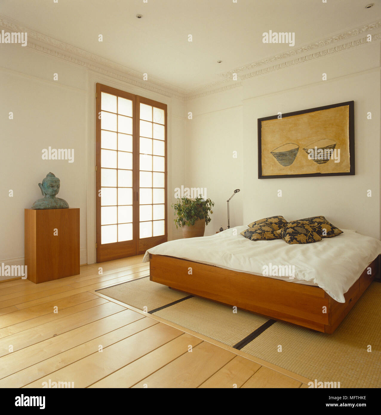 Artwork above wooden double bed in minimalist style bedroom Stock ...