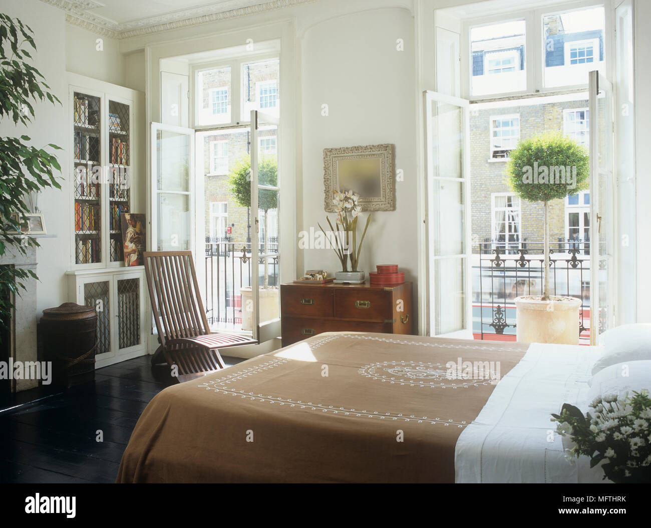 A Bright And Airy Modern Bedroom With A Bed, A Chair, Book Shelf And Side  Cabinet And Potted Trees On A Balcony.