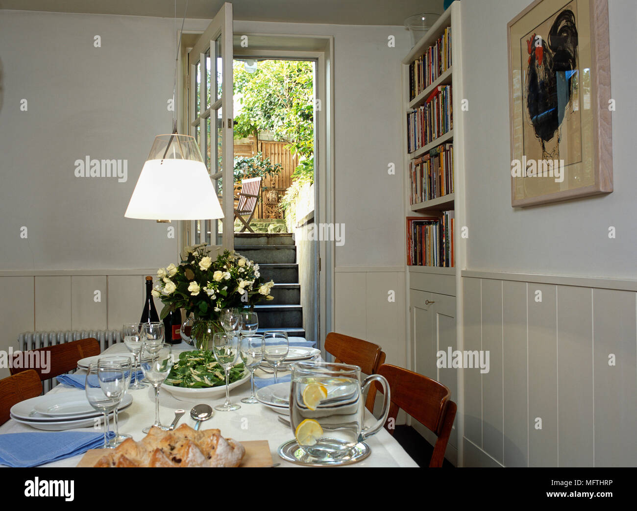 A view of a country dining room with a table set for lunch a lamp