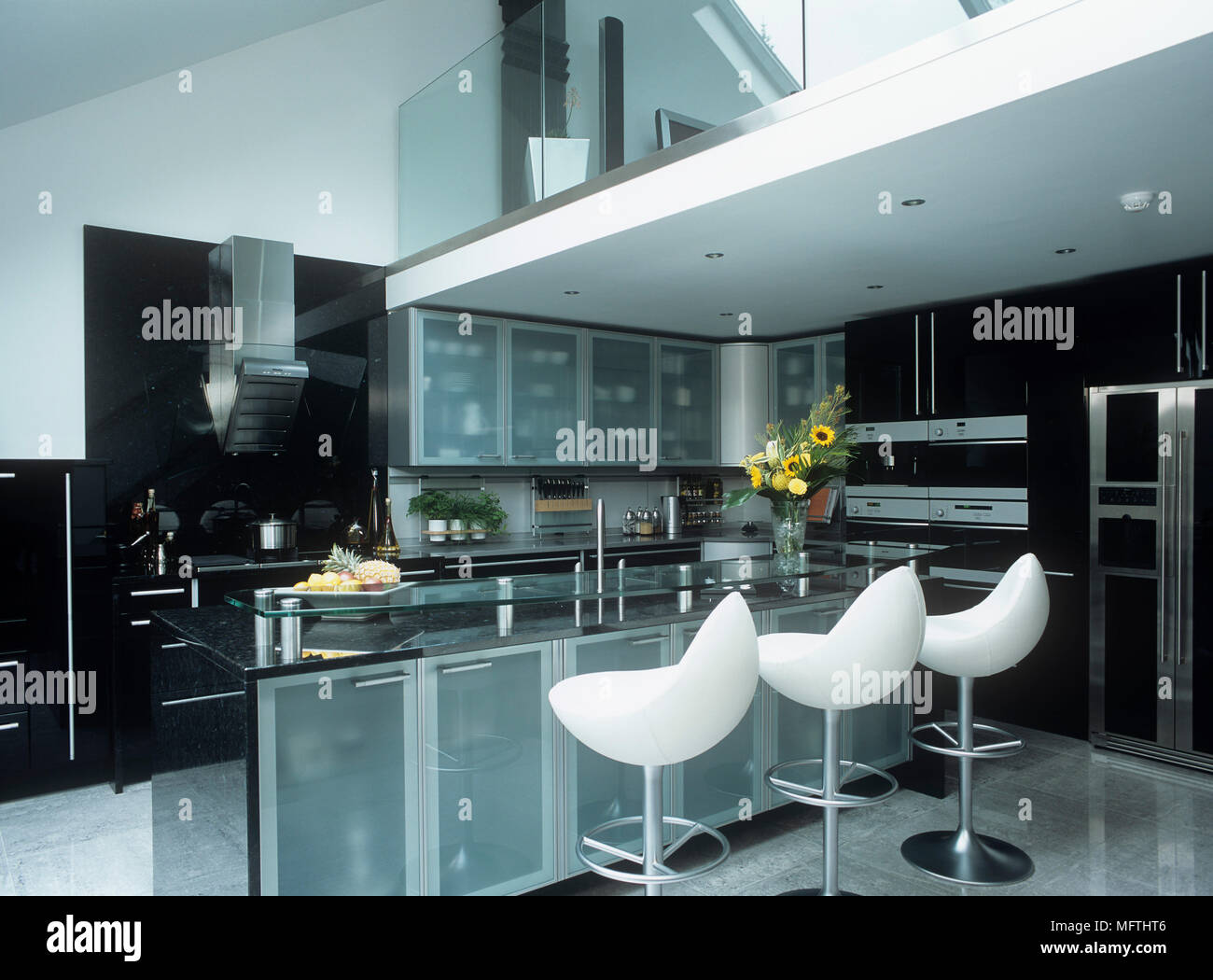 A modern kitchen with black, white, stainless steel and frosted ...