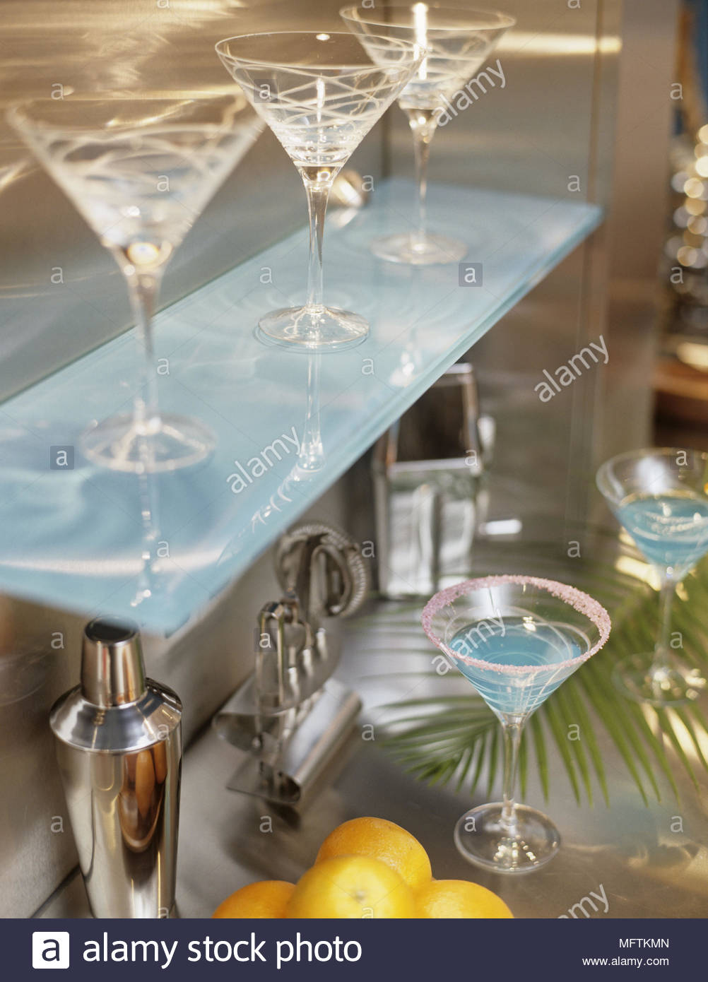 A detail of a modern bar area glass shelf with martini glasses ...